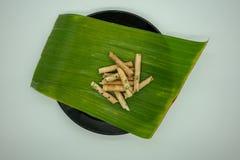 De krul van het kokosnotenkoekje, Rijstbroodjes, op banaanblad en zwarte cerami stock foto's