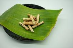 De krul van het kokosnotenkoekje, Rijstbroodjes, op banaanblad en zwarte cerami royalty-vrije stock foto's