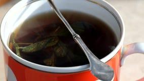 De krullen van de stoomstoom meer dan een kop van hete zwarte thee met munt gaat weg stock video