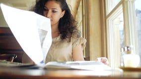 De krullend-haired vrouw zit dichtbij een venster in een koffie en doorbladert een krant stock videobeelden