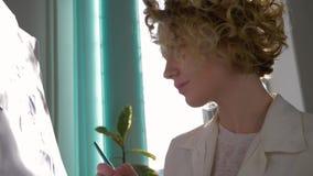 De krullende jonge schildersvrouw met borstel schildert beeld voor hobbys bij kunststudio in natuurlijk licht tegen helder venste stock videobeelden