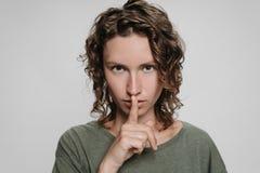 De krullende Kaukasische jonge vrouw bekijkt ernstig, houdend vinger haar lippen gesloten vragen stock afbeeldingen