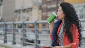 De krullende mooie dame drinkt buiten koffie stock footage