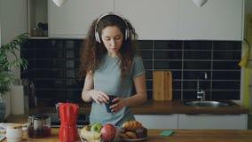 De krullende mooie Kaukasische tiener in hoofdtelefoons dansend prepearing ontbijt, het drinken koffie, zette rode theepot stock videobeelden