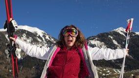 De krullende skiër verheugt zich in de sneeuw tegen de achtergrond van bergen Vrouw in spiegelglazen, skikostuum en skis ter besc stock videobeelden