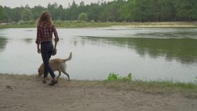 De krullende vrouw loopt met haar hond dichtbij het meer stock footage