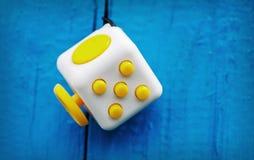 De kubus antistress op een blauwe achtergrond, friemelt Kubus Eenvoudige Spanning Stock Afbeeldingen