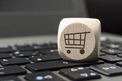 De kubus dobbelt op een toetsenbord met een kar, online winkelend royalty-vrije stock afbeelding
