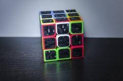 De kubus van Rubik op de donkere lijst stock afbeeldingen