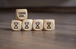 De kubussen dobbelen met uurglazen pictogram en spoedig komst royalty-vrije stock afbeelding