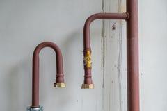 De kuiperpijpen van het verwarmingssysteem met kogelkleppen op een muur stock foto's