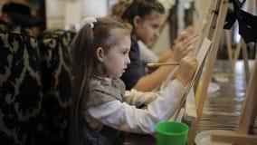 De kunstacademie, een groep kinderen met schildersezels schildert het schilderen met borstels en verven stock video