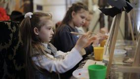 De kunstacademie, een groep kinderen met schildersezels schildert het schilderen met borstels en verven stock videobeelden