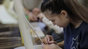 De kunstacademie, een groep kinderen met schildersezels schildert het schilderen met borstels en verven stock footage