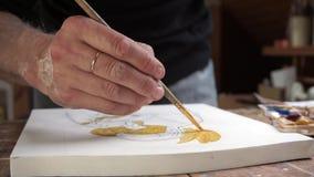 De kunstenaar behandelt zijn schets met een gouden verf stock videobeelden