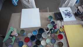 De kunstenaar bereidt een beeld voor Witte verf Mensen in Schorten Art Studio De fles van de nevel stock footage