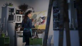 De kunstenaar in de studio het schrijven borstel op canvas stock video