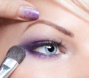 De kunstenaar die van de make-up oogschaduw toepast royalty-vrije stock foto