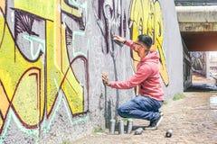 De kunstenaar die van de straatgraffiti met een kleurenaërosol een donkere graffiti van de monsterschedel op de muur in de stad s royalty-vrije stock foto