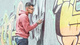 De kunstenaar die van de straatgraffiti met een kleurenaërosol een donkere graffiti van de monsterschedel op de muur in de stad s stock afbeelding