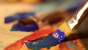 De kunstenaar dompelt de borstel in blauwe verf onder mengt het op het palet stock videobeelden