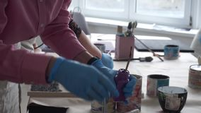 De kunstenaar dompelt de borstel in een kruik van verf onder Art Studio stock footage