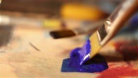De kunstenaar dompelt zijn borstel in blauwe verf onder stock videobeelden