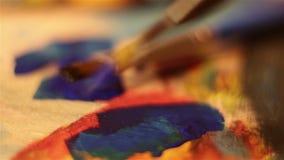 De kunstenaar dompelt zijn borstel in blauwe verf onder stock footage