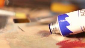 De kunstenaar drukt de blauwe verf van de buis op het palet stock videobeelden