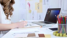 De kunstenaar in haar workshop creeert meesterwerken, trekt schetsen voor de de zomerinzameling stock videobeelden