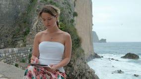 De kunstenaar kijkt omhooggaand en trekt op een blad van verf op de waterkant Mooie vrouw stock video