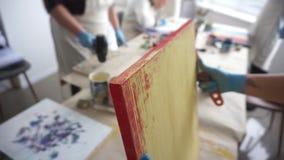 De kunstenaar krast de verf met een spatel De Blikken van de verf Gele verf stock video