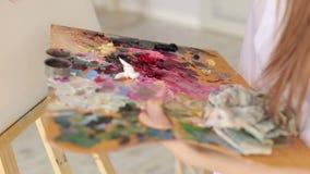 De kunstenaar mengt olieverven op een palet met een borstel stock footage