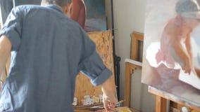 De kunstenaar mengt verf op het palet in het licht van de zon Studioworkshop van een professionele reeks van kunstenaarsGreat van stock footage