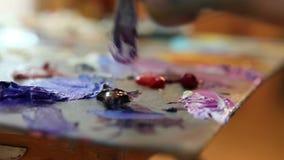 De kunstenaar mengt verf op het palet, Kunstborstel gemengde verf op het palet, het olieverfschilderij van de de mengelingskleur  stock videobeelden