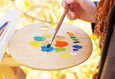 De kunstenaar mengt verf van verschillende kleuren op palet Stock Fotografie
