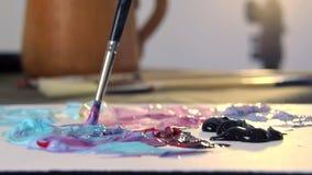 De kunstenaar mengt verschillende kleuren van acrylverf met een borstel voor tekening Voorbereiding van kleuren voor tekeningsbee stock videobeelden