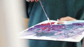De kunstenaar mengt verschillende kleuren van acrylverf met een borstel voor tekening Voorbereiding van kleuren voor tekeningsbee stock video