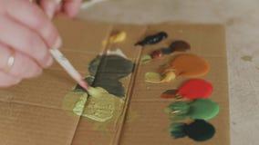 De kunstenaar mengt verven op het palet alvorens een beeld, schilder bij de studio te schilderen, schepper maakt kunststuk stock videobeelden