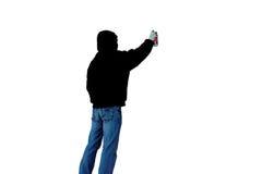 De kunstenaar met kan van nevel schilderen trekt geïsoleerd graffitibeeld op een witte achtergrond in zwarte kap onbekende achter stock foto