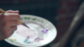De kunstenaar neemt een verfborstel en trekt op canvas Vrouw-kunstenaar stock footage
