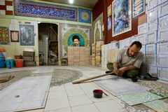 De kunstenaar past het schilderen op de tegels in zijn studio toe Royalty-vrije Stock Afbeelding