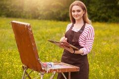 De kunstenaar schildert beeld in openlucht, houdend olieverfborstel en palet van kleuren in hand, die haar creativiteit brengen a stock afbeeldingen