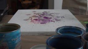 De kunstenaar schildert een abstract beeld De leraar stelt voor Mensen in Schorten Verfblikken en borstels De plonsen van de verf stock video