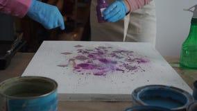De kunstenaar schildert een abstract beeld De leraar stelt voor Mensen in Schorten Verfblikken en borstels De plonsen van de verf stock videobeelden