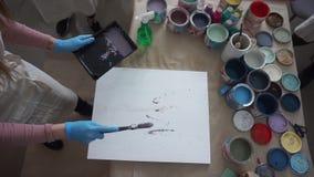 De kunstenaar schildert een abstract beeld Mensen in Schorten Verfblikken en borstels De plonsen van de verf stock video