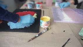 De kunstenaar schildert een abstract beeld met een spons A kan van geel schilderen Gloved Handen Art Studio stock videobeelden
