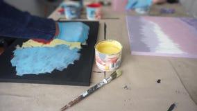 De kunstenaar schildert een abstract beeld met een spons A kan van geel schilderen Gloved Handen Art Studio stock video