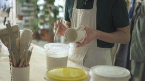 De kunstenaar schildert een borstel met witte verf op een ceramische kop stock videobeelden
