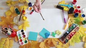 De kunstenaar schildert een heldere gele dag van de zonherfst stock videobeelden